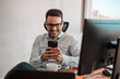 Portrait of a happy smiling businessman in eyeglasses using smartphone while sitting at the office.