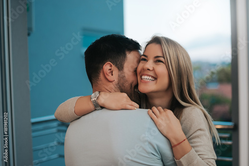 Beautiful lady leans to man's shoulder while he hugs her. Wallpaper Mural