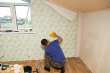 Man Glues The Wallpaper To The...