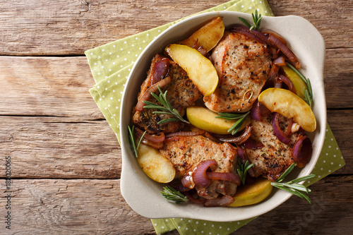 baked pork fillet with green apples, onions and rosemary close-up. Horizontal top view