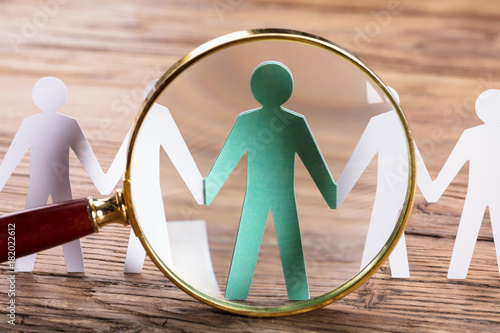Fototapeta Magnifying Glass On Cut-out Figures obraz