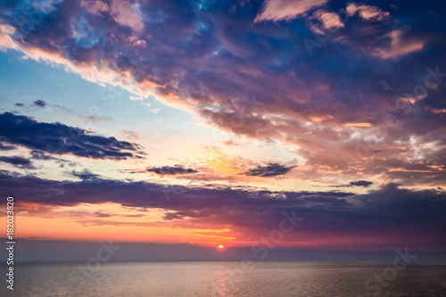 Spoed Foto op Canvas Zee zonsondergang Sunset over calm sea in summer with sun beam