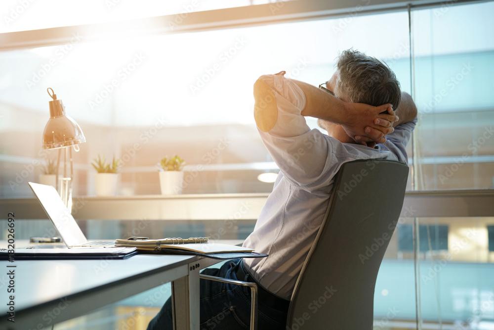 Fototapeta Businessman in office relaxing in chair