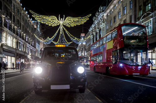 Photo  Red double-decker bus and black cabpass under twinkling Christmas lights along the upscale shopping district of Regent Street
