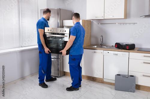 Two Men Fixing Oven In Kitchen Wallpaper Mural
