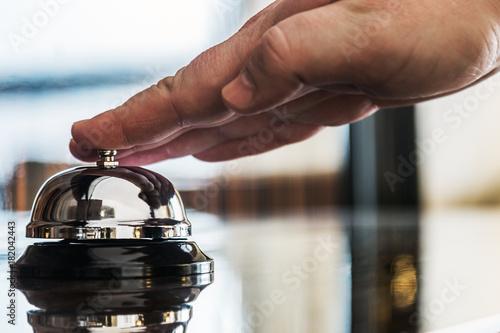 Plakat dłoń naciska dzwonek serwisowy na recepcji w hotelu lub restauracji