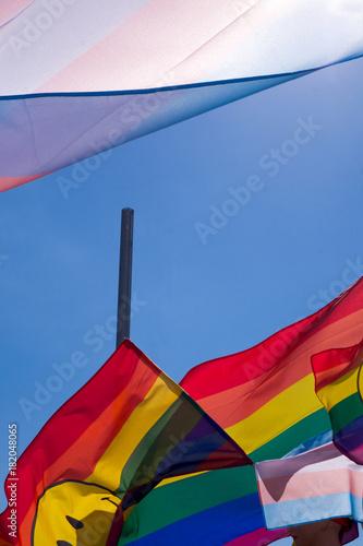 Plakat tęczowe kolorowe flagi pływające w błękitne niebo ze słońcem świeci przez
