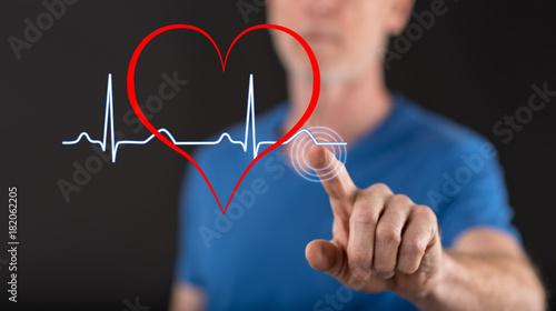 Photo Man touching a heart beats graph on a touch screen
