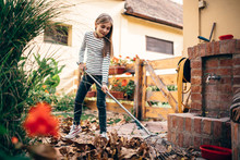Girl Raking Up Autumn Leaves
