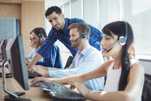 Male supervisor assisting telemarketer at call center