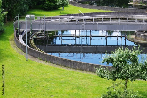 Türaufkleber Darknightsky Sewer Treatment Plant Clarifier Ecology during Spring Season with Blooming Tree