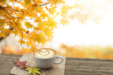 Cup Of Coffee Latte Art On Old Wooden In Autumn With Maple Tree Red Leaves Colorful In The Garden. Seasonal Fall And Beautiful Relax Aroma Concept And Free Space.