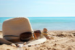 Pyramid of stones to the right of the hat with sunglasses on the sand against the blue sea