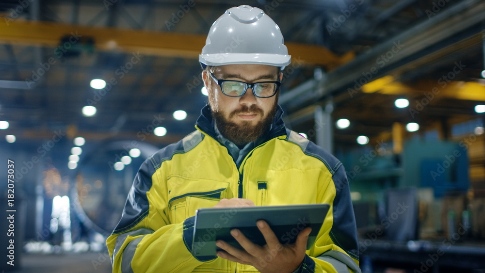 Fototapeta Industrial Engineer in Hard Hat Wearing Safety Jacket Uses Touchscreen Tablet Computer. He Works at the Heavy Industry Manufacturing Factory.