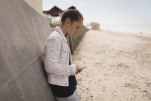 Young Woman Using Mobile Phone While Leaning Against Wall