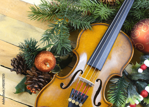 Fotografie, Obraz  A miniature violin surrounded by artificial pine and holly with Christmas balls