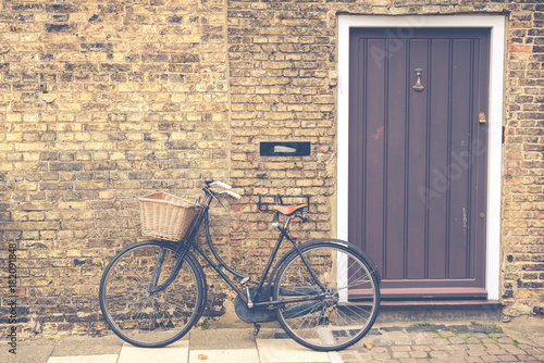 In de dag Fiets Vintage bicycle with retro wicker basket parked in front of a house front door. Matte finish.