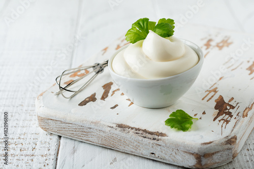 Traditional mayonnaise sauce in white ceramic bowl and ingredients for its preparation on white wooden background. Selective focus.