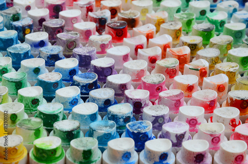 A pattern from a many nozzles from a paint sprayer for drawing graffiti, smeared into different colors. The plastic caps are arranged in many rows forming the color of the rainbow © mehaniq41