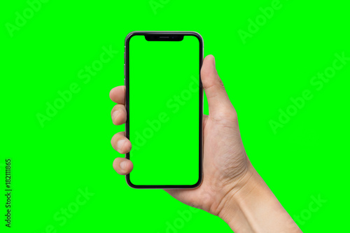 Man's hand shows mobile smartphone with green screen in vertical position isolated on green background - 182111865
