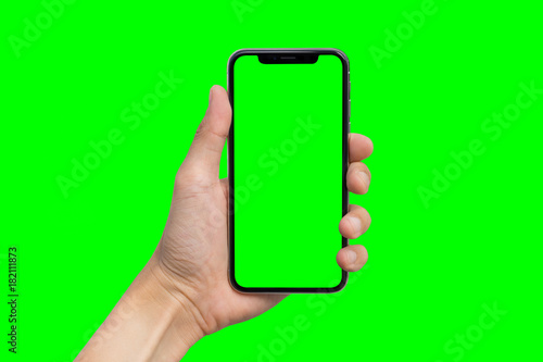 Man's hand shows mobile smartphone with green screen in vertical position isolated on green background - 182111873