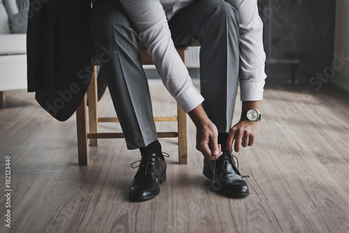 A man in a business suit ties the laces 335.