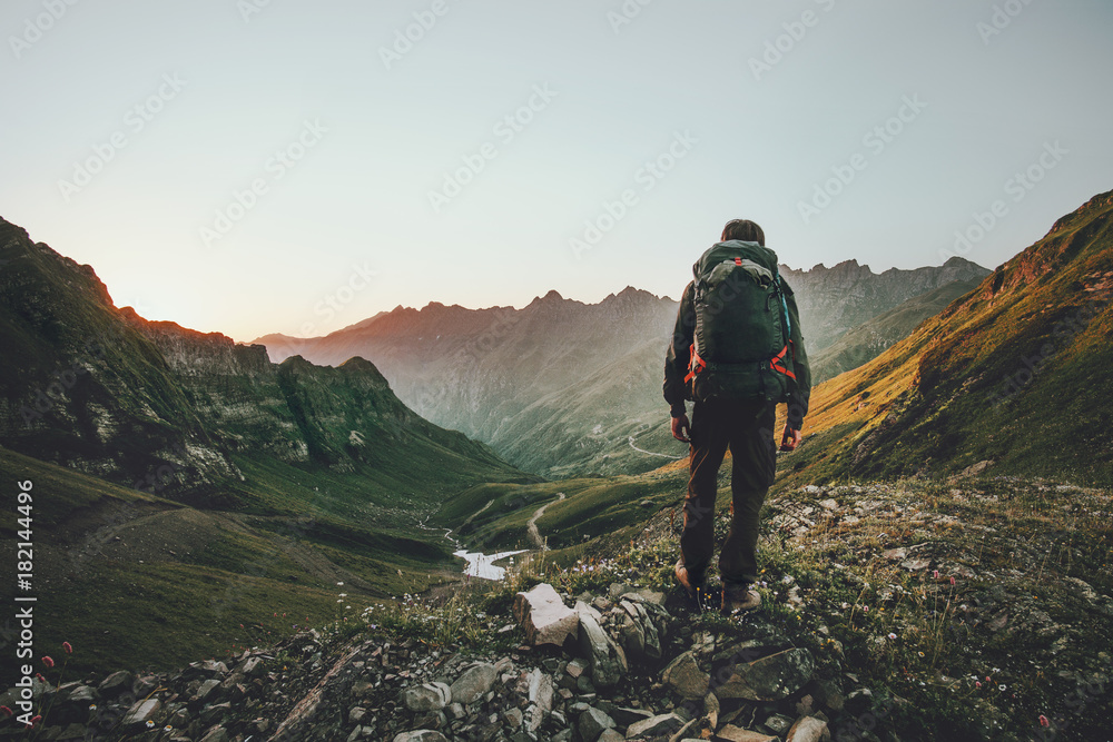 Obraz Man hiking at sunset mountains with heavy backpack Travel Lifestyle wanderlust adventure concept summer vacations outdoor alone into the wild fototapeta, plakat