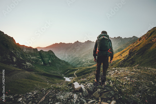 Fototapeta Man hiking at sunset mountains with heavy backpack Travel Lifestyle wanderlust adventure concept summer vacations outdoor alone into the wild obraz