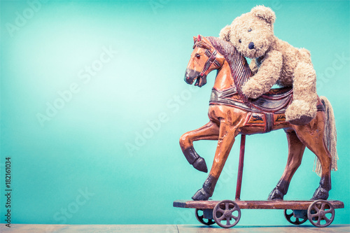 Valokuvatapetti Teddy Bear sitting on vintage antique Christmas wooden horse toy on wheels front mint green wall background