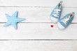 Children's sneakers for a boy of blue color and an star toy on wooden background. Mockup