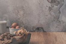 Brown Wooden Table On A Background Of Empty Concrete Wall With Glass Of Milk, Chocolate Muffin, Walnuts, Dried Orange, Anise And Stone Plate