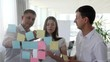 Creative business people with many sticky notes to window working on new project in boardroom