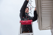 Man Hanging Christmas Lights D...