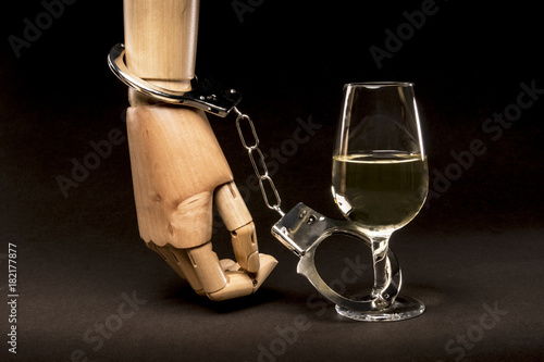 Foto op Canvas Alcohol Hand tied to a glass of alcohol with handcuffs. Concept of addiction to alcohol.