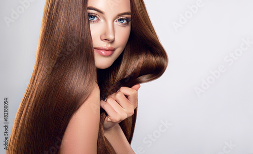 Staande foto Kapsalon Beautiful brunette girl with long straight smooth hair . A woman with healthy straight hairstyle