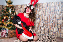Beautiful Young Woman Celebrating Winter Holidays With Her Standard Poodle Puppy.