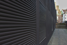 Sidewalk And Black Wall With Large Air Conditioning Vents That Form Converging Lines Leading Towards Distant Steps