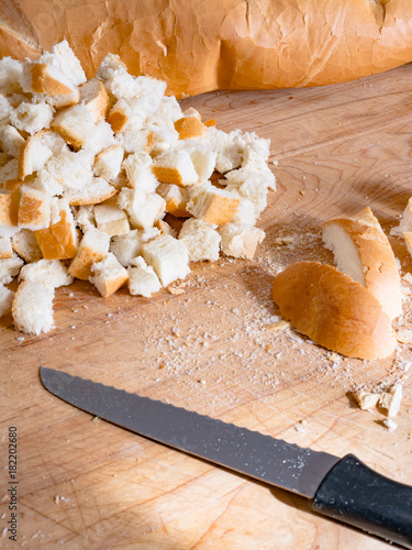 Fotografie, Obraz  Cutting Bread Cubes on Wood Board