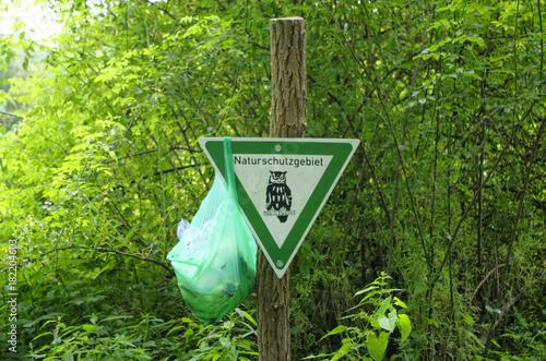 Fotografía  Abfall im Naturschutzgebiet - Warnschild Naturschutzgebiet, an das eine Tasche m