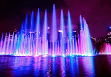 The Colorful Of Fountain On The Lake At Night, Near By Petronas Twin Towers And Suria Klcc Shopping Centre; With City On Background. Kuala Lumpur, Malaysia.