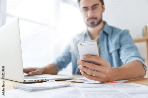 Modern smart phone in man`s hands. Young hipster guy with beard monitors news for website uses mobile phone, free internet and laptop computer. Skilled male journalist messages with chief editor