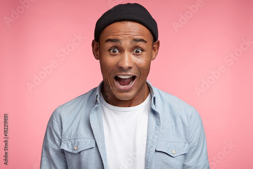 Vászonkép  Excited amazed mixed race male wears black hat and stylish shirt, being overjoyed and happy to see present, isolated over pink background
