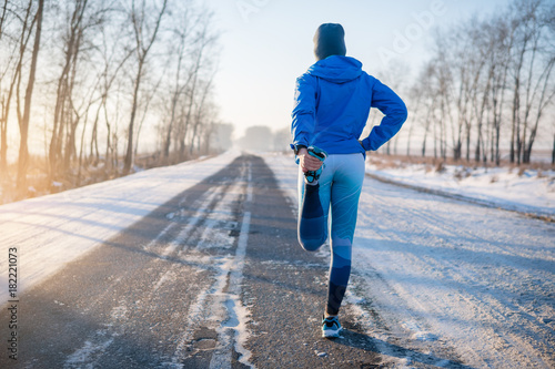 La pose en embrasure Glisse hiver Runner stretching in winter Park. A healthy way of life.