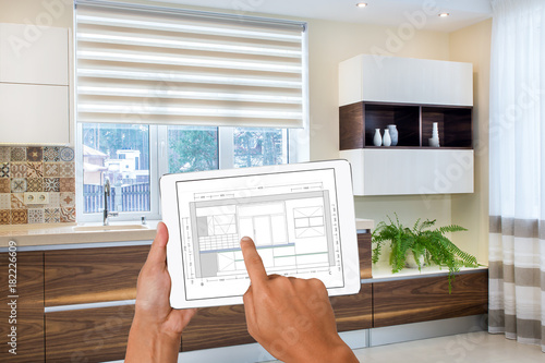 Beautiful Hands Holding Tablet With Kitchen Drawing. In The Background Real Finished  Kitchen Interior Design.