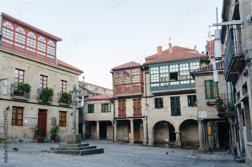 Historic square in Pontevedra. Buildings with coloured facade wooden windows balconies and a stone croos in the middle.