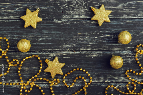 Fototapeta Gold stars and Christmas balls on a black wooden background. obraz na płótnie