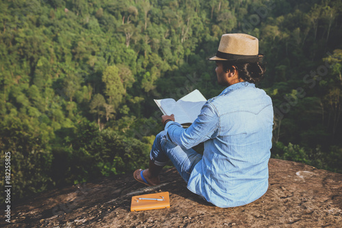 Egypt Asian man travel relax in the holiday. seats relax read books on rocky cliffs. On the Moutain. In Thailand