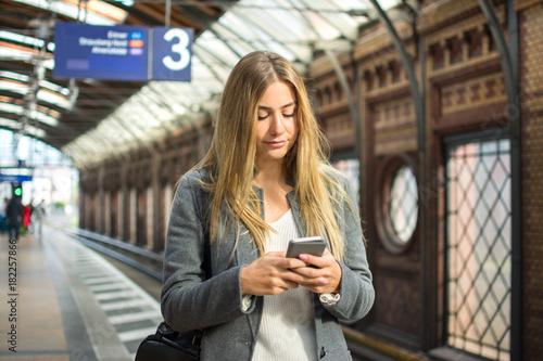 Plakat Młoda kobieta używa telefon komórkowego podczas gdy czekający pociąg przy stacją kolejową.
