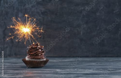 Tasty chocolate cupcake with sparkler on wooden table Wallpaper Mural