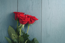 Three Red Roses On Blue Wood Table With Copy Space
